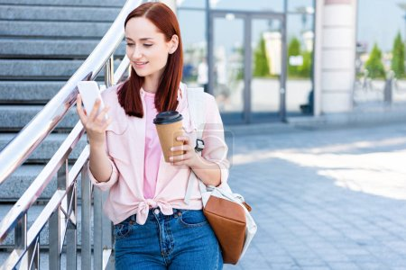 Photo for Attractive redhair woman in pink shirt using smartphone and holding disposable coffee cup on street - Royalty Free Image