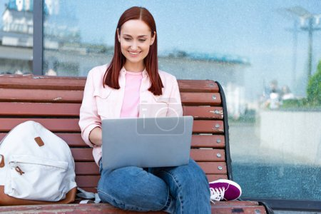attractive smiling redhair freelancer using laptop on bench in city