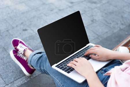 Photo for Cropped image of freelancer using laptop with blank screen on street - Royalty Free Image
