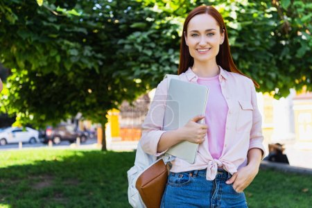 attractive cheerful freelancer holding laptop and looking at camera in park