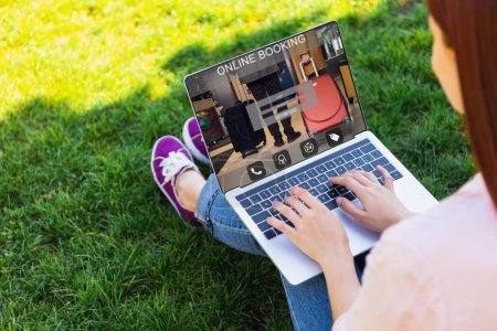Photo for Cropped image of woman using laptop with online booking appliance in park - Royalty Free Image