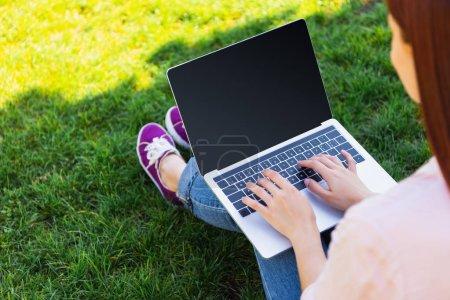 Photo pour Image recadrée de pigiste à l'aide d'un ordinateur portable avec écran blanc dans le parc - image libre de droit