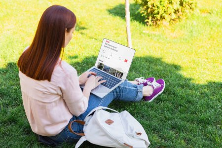 attractive woman using laptop with loaded airbnb page in park