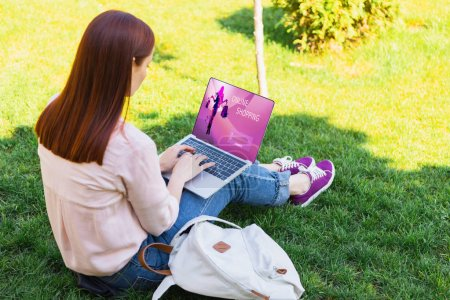 Photo for Attractive woman using laptop with online shopping appliance in park - Royalty Free Image