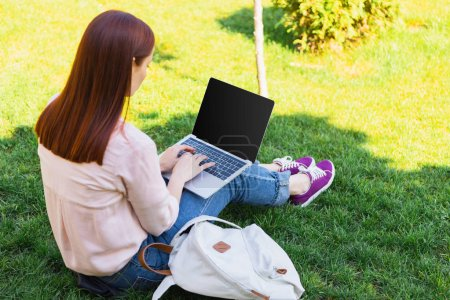 attractive freelancer using laptop with blank screen in park