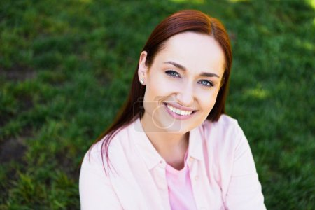 portrait of attractive redhair woman in pink shirt looking at camera in park