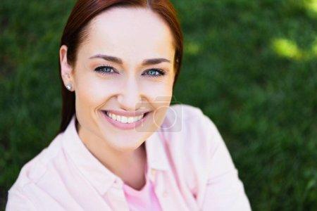 Kopf und Schultern einer attraktiven, glücklichen Rothaarigen im rosa Hemd, die im Park in die Kamera schaut