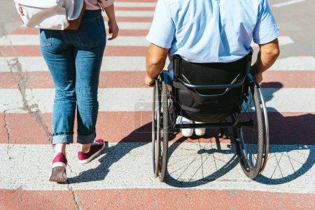Foto de Imagen recortada de novio en silla de ruedas y peatones del cruce de novia en la ciudad de - Imagen libre de derechos
