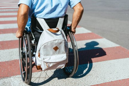 Photo for Cropped image of disabled man in wheelchair with bag riding on crosswalk - Royalty Free Image