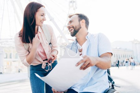 laughing handsome boyfriend in wheelchair holding map and looking at girlfriend on street