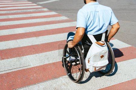 cropped image of man using wheelchair on crosswalk on street