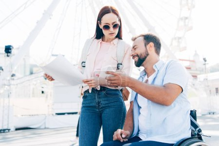 handsome boyfriend in wheelchair using smartphone and girlfriend standing with map on street