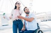 handsome boyfriend in wheelchair showing smartphone to girlfriend with map on street