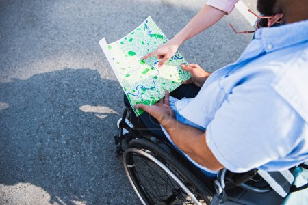 Photo for Cropped image of boyfriend in wheelchair holding map and girlfriend pointing on location on street - Royalty Free Image