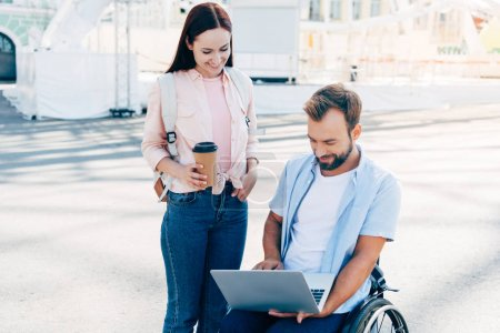 smiling handsome boyfriend in wheelchair using laptop and girlfriend standing with coffee in paper cup on street