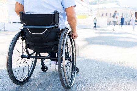 Photo pour Image recadrée de l'homme en fauteuil roulant dans la rue - image libre de droit
