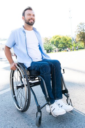 handsome smiling man using wheelchair on street and looking up