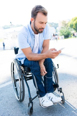 handsome man in wheelchair listening to music with smartphone on street