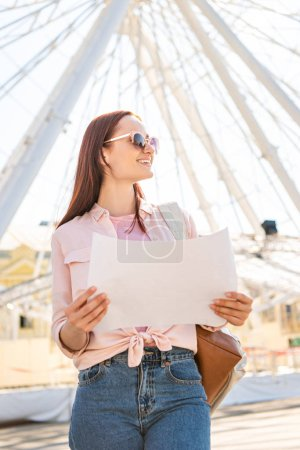 smiling attractive tourist in sunglasses standing with map near ferris wheel in amusement park and looking away