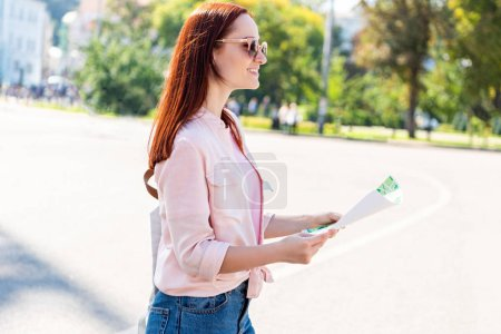 Photo for Side view of attractive smiling traveler in sunglasses standing with map on street - Royalty Free Image