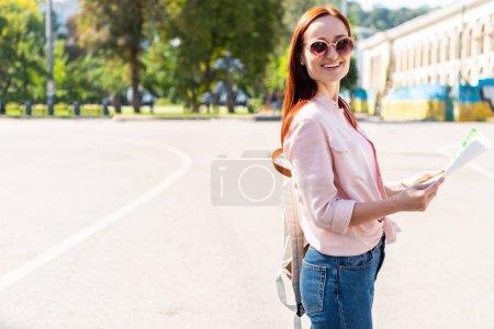 Photo pour Heureux touristique attrayante en lunettes de soleil permanent avec carte sur la rue et de regarder la caméra - image libre de droit