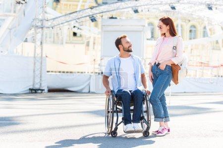 Foto de Apuesto novio en silla de ruedas y novia mirando el uno al otro en la calle - Imagen libre de derechos