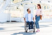 handsome boyfriend in wheelchair and girlfriend looking at each other on street