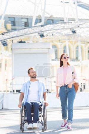Foto de Apuesto novio en silla de ruedas y atractiva novia caminando en la calle - Imagen libre de derechos