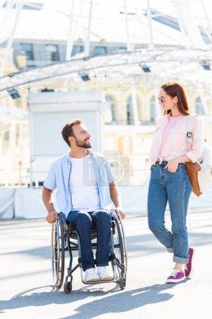 Foto de Novio guapo sonriente en silla de ruedas y novia mirando el uno al otro en la calle - Imagen libre de derechos