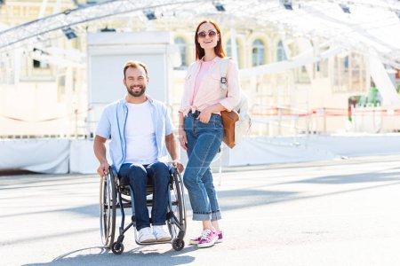 Foto de Feliz guapo novio en silla de ruedas y la novia mirando a cámara en la calle - Imagen libre de derechos