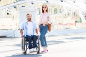 happy handsome boyfriend in wheelchair and girlfriend looking at camera on street