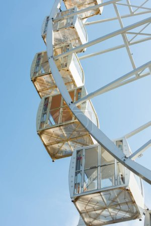 cabins of observation wheel against blue sky in amusement park