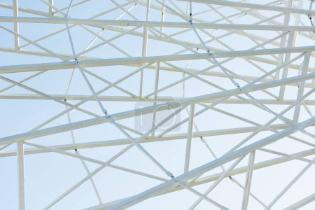 metallic parts of observation wheel construction against blue sky