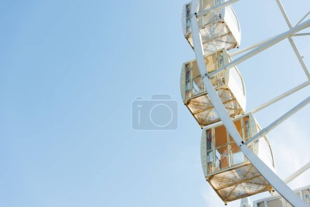cabins of ferris wheel against blue sky in amusement park