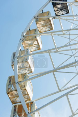 low angle view of cabins of observation wheel against blue sky in amusement park