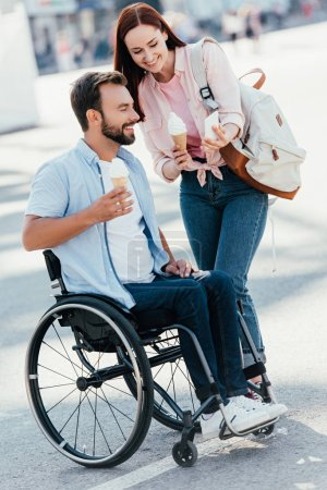 Photo for Girlfriend with ice cream showing something on smartphone to handsome boyfriend in wheelchair on street - Royalty Free Image