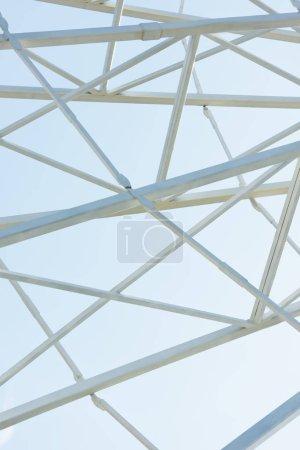 metallic parts of observation wheel construction against blue sky in amusement park