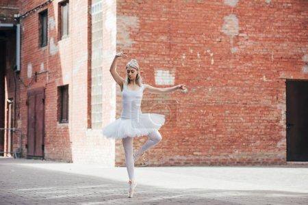 Photo pour Vue sur toute la longueur belle élégante jeune ballerine danse sur la rue de la ville - image libre de droit