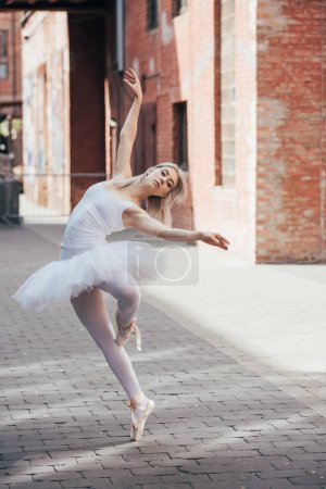 Photo for Beautiful elegant young ballerina looking at camera while dancing on city street - Royalty Free Image