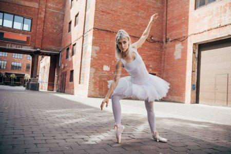 elegant young ballerina dancing in urban city street