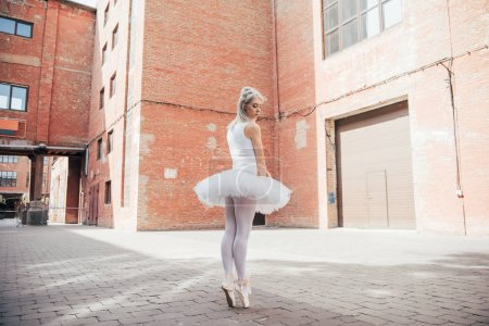 full length view of young ballerina in white tutu and pointe shoes dancing on street