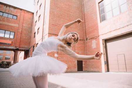 low angle view of young ballerina in white tutu dancing on street