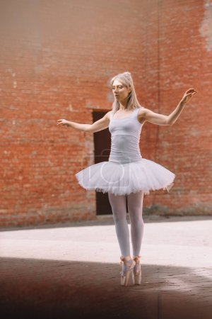 full length of young ballerina in white tutu and pointe shoes dancing on street