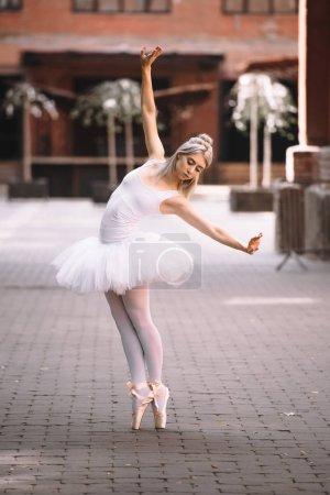 beautiful young ballerina in tutu skirt dancing on city street