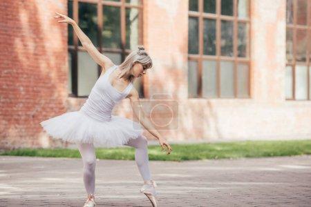 attractive young ballerina in tutu skirt dancing on urban street