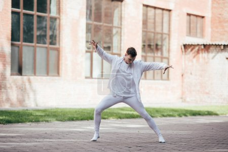 handsome young dancer performing contemporary dance on street