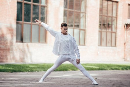 Photo for Handsome young dancer performing modern dance on street - Royalty Free Image