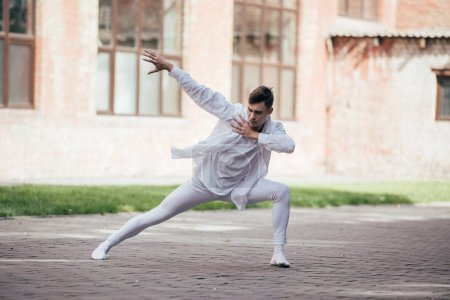 handsome young man dancer in white clothes dancing on urban city street