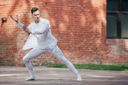 Photo for Young male ballet dancer in white clothes dancing on urban street - Royalty Free Image