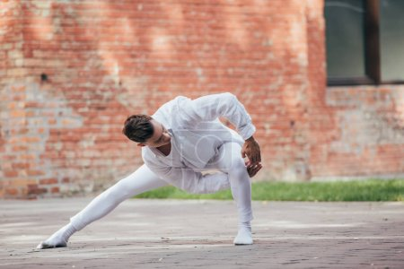 Photo for Handsome young male dancer in white clothes dancing on urban street - Royalty Free Image